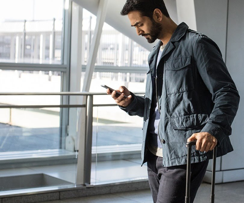 Man standing at airport while looking at his phone